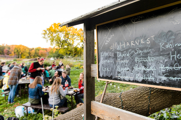 A chalkboard displays different types of produce harvested from the gardens, while students enjoy a meal together in the background.