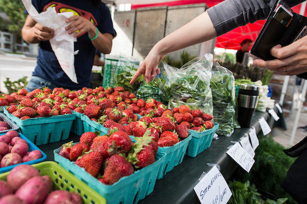 A shopper points to a pint of strawberries for purchase at the Farmers Market.