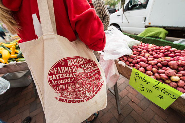 "A shopper at the Dane County Farmers Market with a bag showing the Capitol and the text, ""Madison, Wisconsin""."