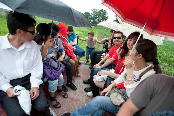 Smiling students sit together in a wagon, some holding umbrellas.
