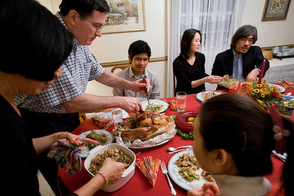 People sit together around a table draped with a red tablecloth while one person carves a turkey on the table.