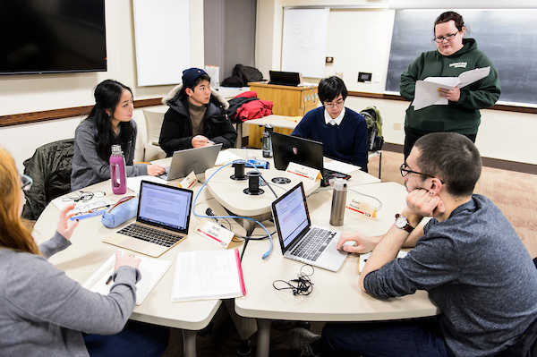 Students cluster around a table with open laptops while a graduate student stands and leads a discussion.