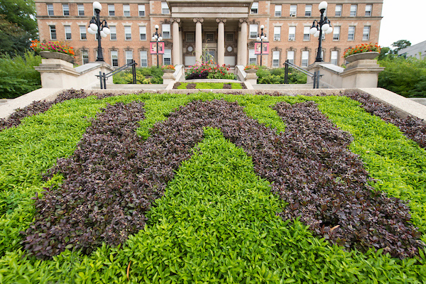 "A flowerbed planted in the shape of a ""W"" in front of Agricultural Hall."