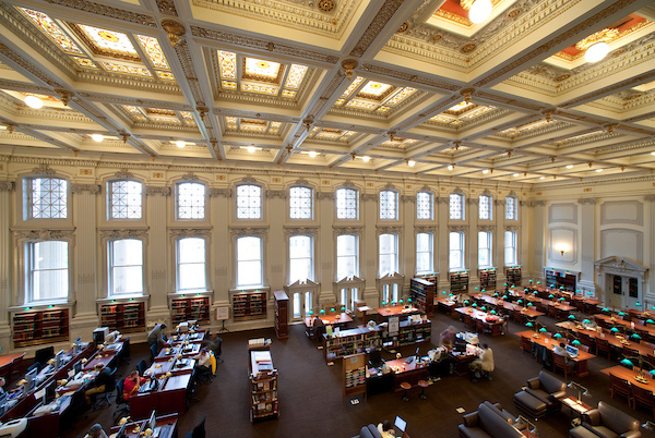 Rows of study tables are dwarfed by high ceilings and grand windows in this reading room and library.