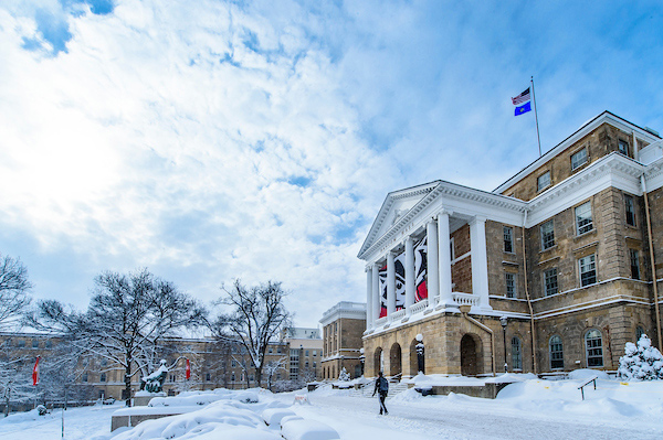 Snow covers the ground and some walkways in front of Bascom Hall.