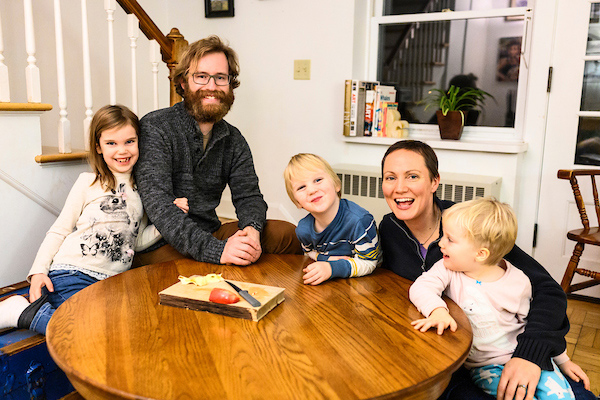 Two adults and three children sit around a table in their home, smiling for the camera.