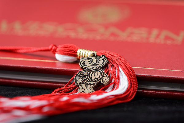 A Bucky Badger pendant rests on a red and white graduation tassle, with a Wisconsin diploma cover in the background.