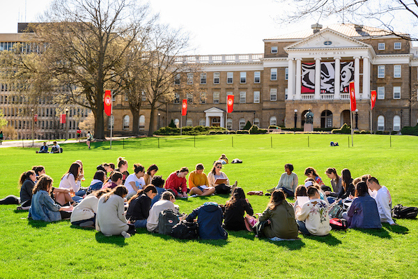 A circle of students sit on Bascom Hill with the Bucky banner on Bascom Hall in the background.