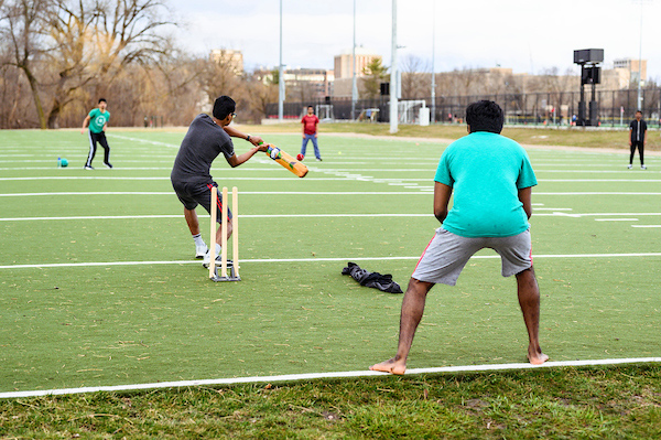 Students playing cricket.